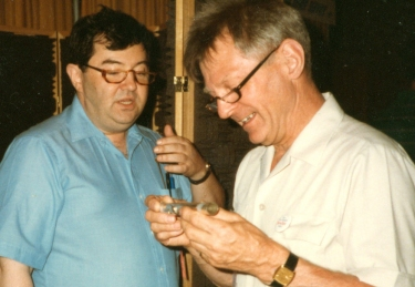 Sandy Drelinger (left) discusses blow-edge technology with Albert Cooper (right) at a flute show display circa mid 1980s.